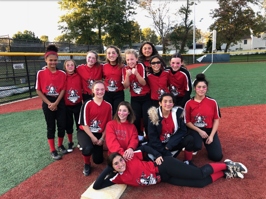 LADY+WARRIORS%3A+The+softball+team+poses+in+front+of+the+field+they+played+at.