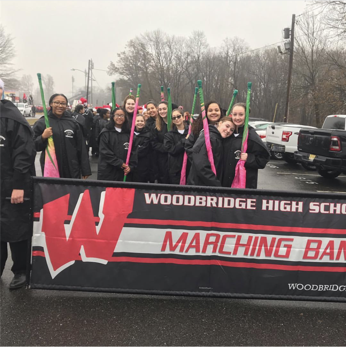 Woodbridge High-schoolers and middle schoolers in marching band smile for the camera.
