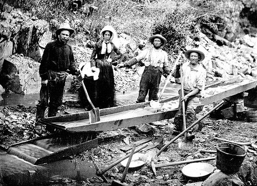 Photo via  https://commons.m.wikimedia.org/wiki/File:1850_Woman_and_Men_in_California_Gold_Rush.jpg Under the Creative Commons License