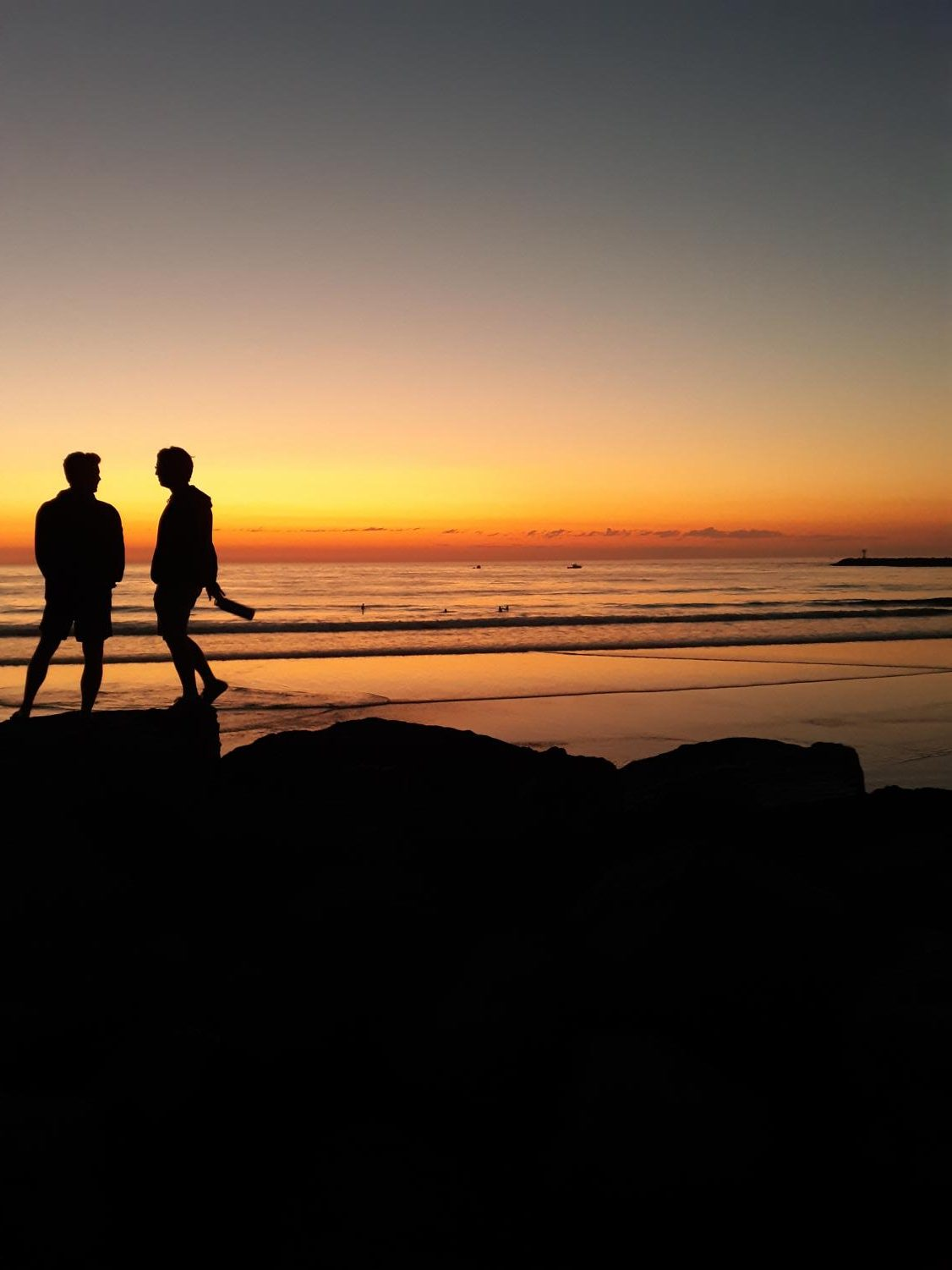 This photo was taken at a beach in San Diego, California.  In the picture there are two silhouettes, standing on rocks at the beach. The sunset is orange and yellow in  which is reflecting onto the ocean, making the it look orange. The purple and dark blue was starting to creep in at the top, signaling that the sun would soon set and the day would soon end.