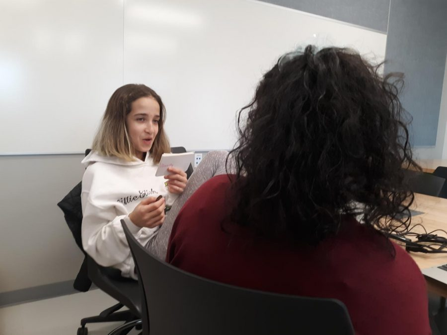 Kenza Kharbouche  and Candace Pinto are sitting at a table, helping each other study for a vocabulary test. They are working in partners