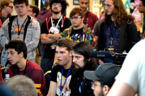 Professional Super Smash Bros. Melee player Mang0 (black hair and beard) at a tournament. Labeled for reuse via https://commons.wikimedia.org/wiki/File:Mango_and_smash_players_-_Connor_Smith_-_TBH.jpg under the Creative Commons License