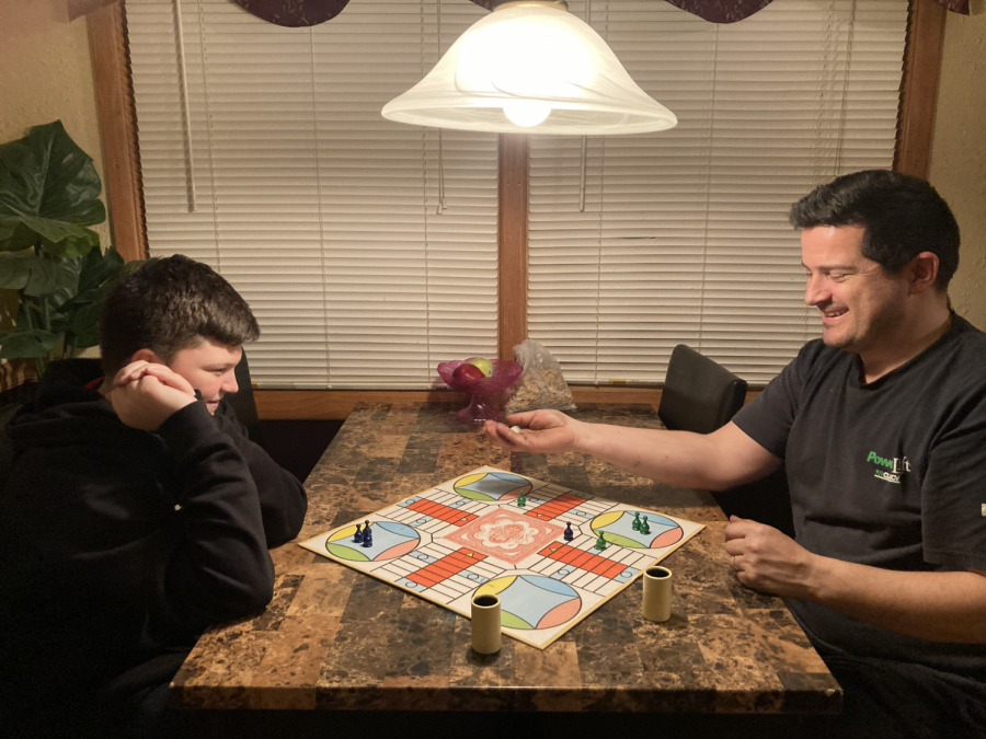 BORED? PLAY A BOARD GAME!: Father and son, Dave and David Vincent, spend quality time together playing a round of Parcheesi during time off.